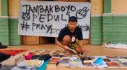 Salah satu anggota Perpusjal Tambakboyo sedang menata lapak baca buku. Foto: Alfan/Progresnews.id.