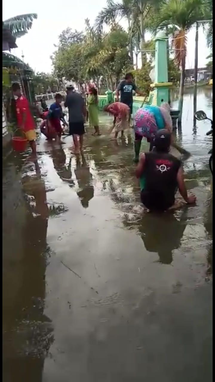 Nampak warga yang membersikan sisa banjir di depan masjid yang berada di tengah pemukiman warga. (Foto: Tangkapan Layar Vidio, Warga Desa Weduni)