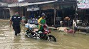 Salah satu lokasi banjir di Lamongan, terlihat Kasi Tanggap Bencana BPBD sedang membangu warga yang motornya mogok. (Foto: Ammy)