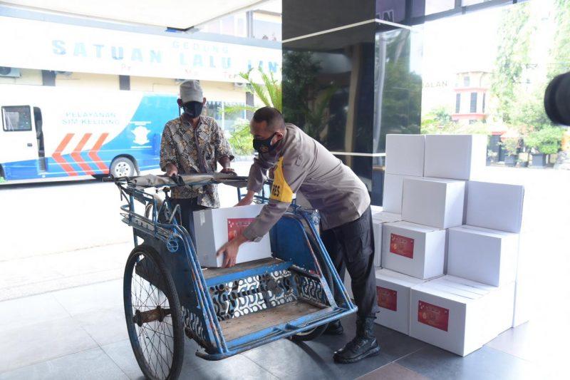 Kapolres Lamongan, AKBP Miko Indrayana saat menyerahkan parsel ke tukang becak. Foto: Ist.