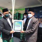 Berkhidmat. Ketua DPC PKB, H Abdul Qodir menyerahkan bantuan kepada AMTV NU diterima KH Chusnan Ali, usai upacara HSN 2021 (23/10). Foto: Chidir/Progresnews.id